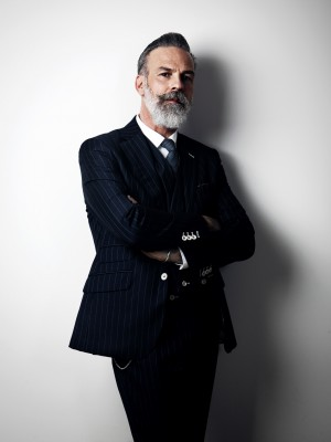 Stylish middle aged man wearing trendy suit, stands against a wall. Vertical